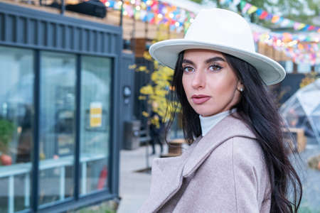 Closeup headshot of beautiful woman in autumn. Young brunette woman with makeup and white hat.