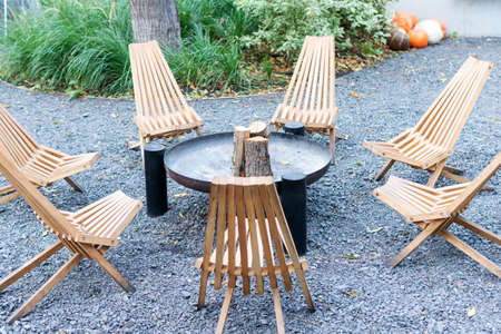 Wooden chairs arranged in a circle. Resting place with fireplace and chairs around. Standard-Bild