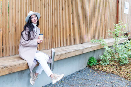 beautiful woman in a coat with a cup of coffee in hand sits by the fence