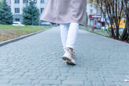 Woman in sneakers and coat walks into the distance. Woman in sneakers and coat walks into the distance.
