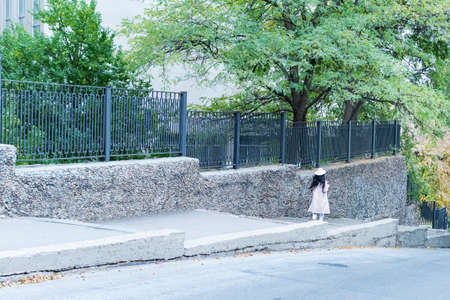 A woman in a coat and hat walks down the street along the fence Standard-Bild