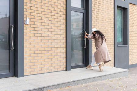 Woman in coat pulls the door