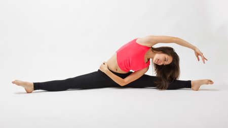 Healthy young sportswoman does the exercises doing the splits looking and holding one hand up and putting aside on white background