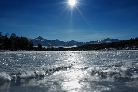 Panorama of frozen lakes, covered with ice and snow. In clear weather with a blue sky in the sunlight. Altai, Ulagan Pass.