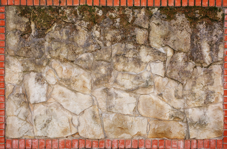 Wall of natural light stone in a red brick frame. Background, texture