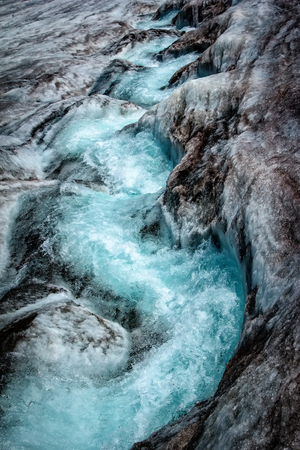 a glacier with a blue fracture, the flow of blue water over the snow. Global warming