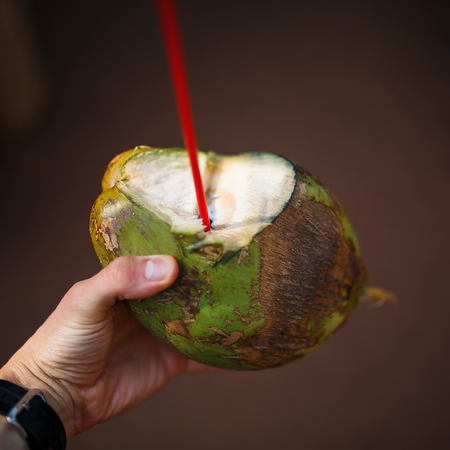 Hand holding out a fresh young green coconut opened with a straw put in it, with the text Bula Fiji written on the coconut. Banco de Imagens