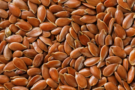 Background texture of seeds of dark brown flax. Grain on butter. Useful cereals.
