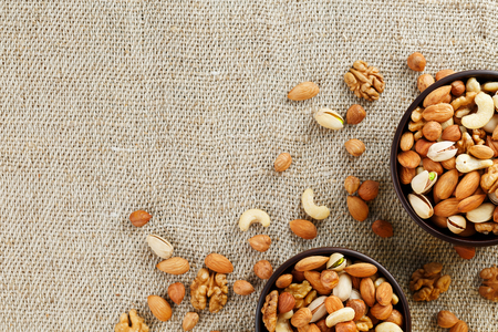 A mixture of cashew nuts, almond nuts, pistachios, hazelnuts and walnuts in a wooden cup against the background of burlap fabric. Nuts as structure and background, macro. Two cups of nuts.