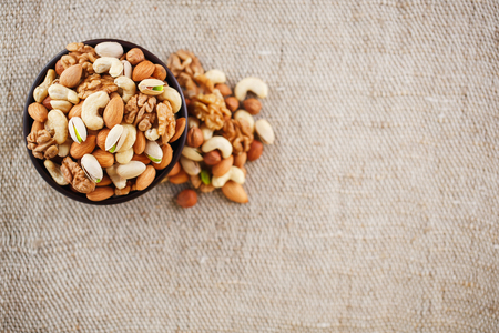 Mix of nuts of cashew, almonds, pistachios, hazelnuts and walnuts is against the background of brown fabric of burlap. Nuts as structure and background, macro