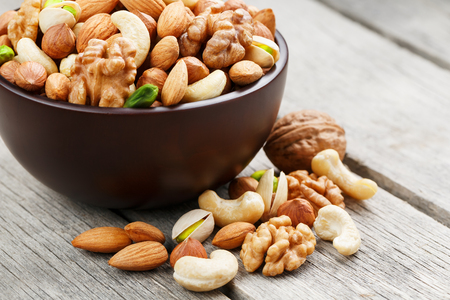 Wooden bowl with mixed nuts on a wooden gray background. Healthy food and snacks, organic vegetarian meals. Walnut, pistachios, almonds, hazelnuts and cashews, walnut.