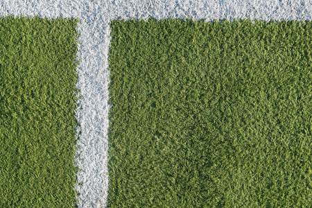 White strip in the field for football. Green texture of a football, volleyball and basketball field.