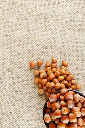 Peeled hazelnuts in a wooden, dark brown cup on a burlap cloth. Super Food, Raw. View from above.