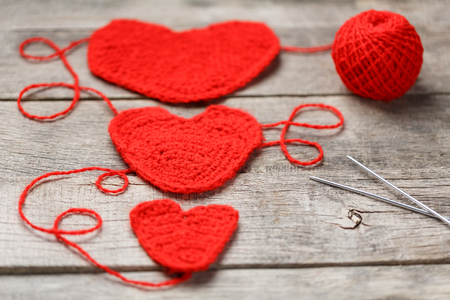 Three red knitted hearts on a gray wooden background, symbolizing love and family. Family relationship, bonds. Valentine's Day. Knitting needles and a ball of thread. Reklamní fotografie