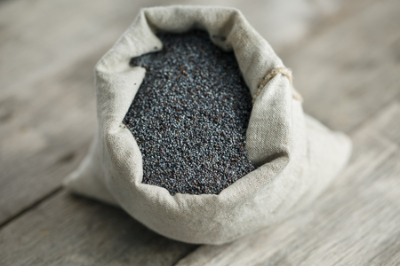 Poppy seeds in a burlap bag on a vintage wooden gray background. In country style. The tasty and useful seeds rich with protein and oils. It is poured out of a bag. Calcium content leader