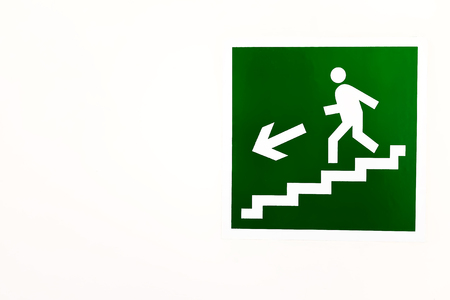 A green sign down the stairs on an empty bright wall. DIRECTION TO THE EMERGENCY EXIT ON THE LADDER DOWN
