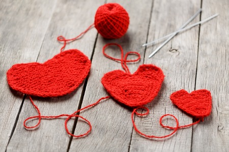 Three red knitted hearts on a gray wooden background, symbolizing love and family. Family relationship, bonds. Valentines Day. Knitting needles and a ball of thread. 版權商用圖片