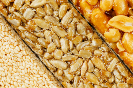 Assorted kozinaki, sweets from sunflower seeds, sesame and peanuts filled with brilliant glaze. Macro close up