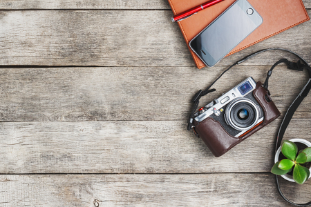 Classic camera with blank notepad page and red pen on gray wooden, vintage table with telephone and green flower. Brown notebook. The concept of the list for the photographer in travels. Free space in country style