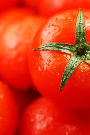 Fresh cherry tomatoes with closeup. Background red tomatoes. A group of juicy ripe fruits. red tomatoes background. Wallpaper tomato macro