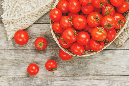Fresh red tomatoes in a wicker basket on an old wooden table. Ripe and juicy cherry tomatoes with drops of moisture, gray wooden table, around a cloth of burlap. In a rustic style. Close-up Low contra 写真素材