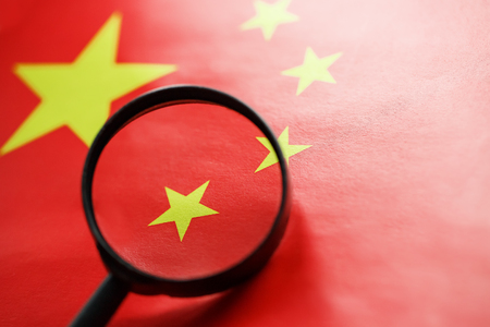 The People's Republic of China a flag is watched through magnifying glass. Spies and observation of People's Republic of China. Monitoring of a condition of China. Concept of danger of theft of military terrorism