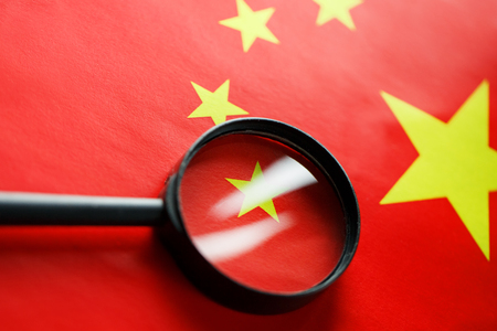 The flag of the CHINESE PEOPLES REPUBLIC is looking through a magnifying glass. The study of the history and culture of a large country and the people of China. The concept of studying the geography, customs Stock Photo