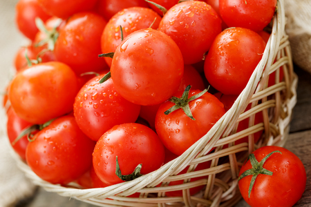 Small red tomatoes in a wicker basket on an old wooden table. Ripe and juicy cherry and burlap cloth, Terevan style country style. selective focus