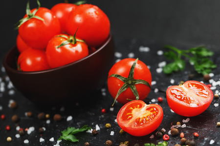 Fresh Sliced Cherry Tomatoes on a black background with spices coarse salt and herbs Reklamní fotografie
