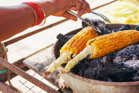 Corn cobs on the grill. Close-up image with corns and hands. Asian, Indian and Chinese street food. Trolley on the beach GOA. Banque d'images