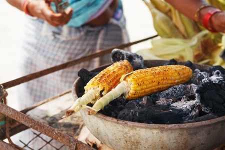 Corn cobs on the grill. Close-up image with corns and hands. Asian, Indian and Chinese street food. Trolley on the beach GOA. Stock Photo