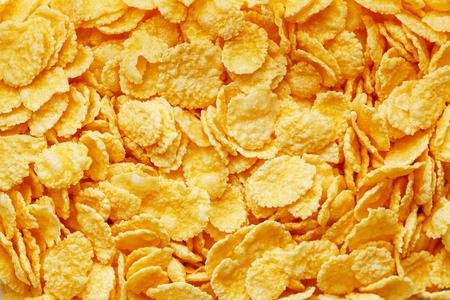 Fondo y textura dorados de los copos de maíz. Vista desde arriba. desayuno saludable de copos de maíz.