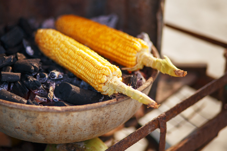 Corn cobs on the grill. Close-up image with corns and hands. Asian, Indian and Chinese street food. Trolley on the beach GOA.