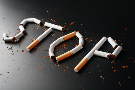 The inscription STOP from cigarettes on a black background. Stop smoking. The concept of smoking kills. Motivation inscription to quit smoking, unhealthy habit. Smoking as a deadly habit, nicotine poison, cancer and smoking Standard-Bild