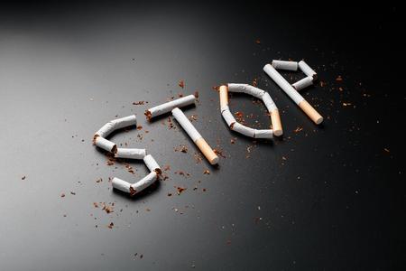 Die Aufschrift STOP von Zigaretten auf schwarzem Hintergrund. Aufhören zu rauchen. Das Konzept des Rauchens tötet. Motivationsinschrift, mit dem Rauchen aufzuhören, ungesunde Gewohnheit. Rauchen als tödliche Angewohnheit, Nikotingift, Krebs und Rauchen Standard-Bild
