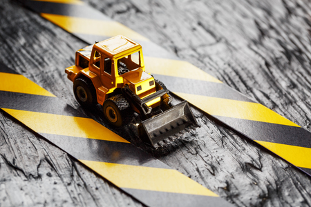 Yellow toy bulldozer on a black background texture. Black and yellow fence tape against the background of the CONCEPT. Business, repair, services. Фото со стока - 120816118