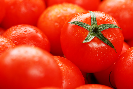 Ripe red tomatoes, with drops of dew. Close-up background with texture of red hearts with green tails. Fresh cherry tomatoes with green leaves. Group of juicy ripe fruit. Imagens