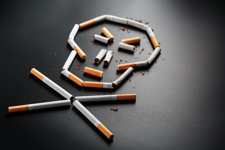 Skull from cigarettes on a black background. The concept of smoking kills. Toward the concept of smoking as a deadly habit, nicotine poisons, cancer from smoking, illness, quit smoking. Copy space