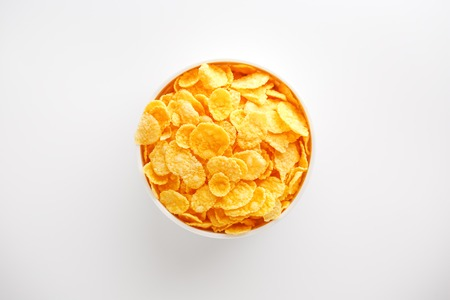 White cup with golden corn flakes, isolated on white background. View from above. Delicious and healthy breakfast. Vertical frame View from above. Delicious and healthy breakfast