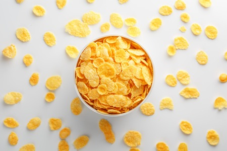White cup with golden corn flakes, isolated on white background. Hopya crumbled around the cup. View from above. Delicious and healthy breakfast Foto de archivo