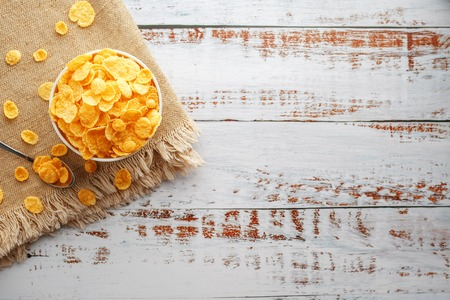 Bowl with golden flakes on a linen, on a light wooden table, next to a spoon. Rustic country style. View from above. White cup, morning healthy breakfast of corn Reklamní fotografie