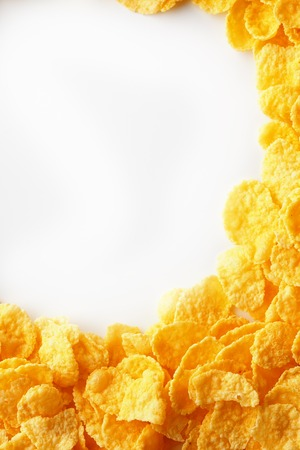 Golden Cornflakes full frame with empty round copy space in the middle as viewed from above. View from above.