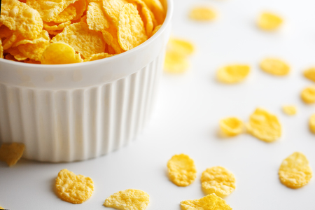 White cup with golden corn flakes, isolated on white background. Hopya crumbled around the cup. View from above. Delicious and healthy breakfast 版權商用圖片
