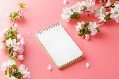Blooming spring sakura on a pink background with notepad space for greeting message. The concept of spring and mother's day. Beautiful delicate pink cherry flowers in springtime. View from above