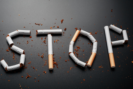 The inscription STOP from cigarettes on a black background. Stop smoking. The concept of smoking kills. Motivation inscription to quit smoking, unhealthy habit. Smoking as a deadly habit, nicotine poison, cancer and smoking