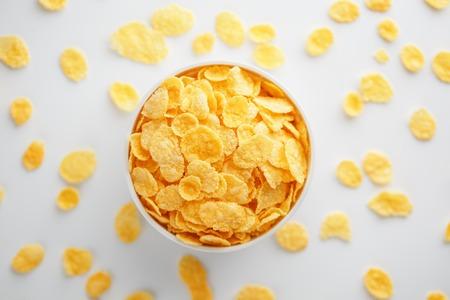 Taza blanca con copos de maíz dorados, aislado sobre fondo blanco. Hopya se derrumbó alrededor de la taza. Vista desde arriba. Desayuno delicioso y saludable