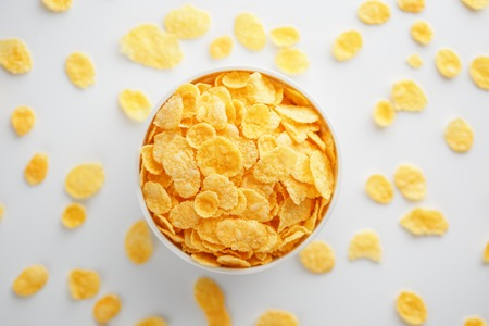 White cup with golden corn flakes, isolated on white background. Hopya crumbled around the cup. View from above. Delicious and healthy breakfast Reklamní fotografie