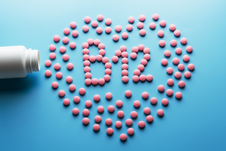 Pink tablets in the form of B12 in the heart on a blue background, spilled from a white can. Food supplement concept Imagens