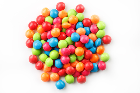 A rainbow of colors from multicolored candies close-up, multi-colored glaze dragee on a white background isolated. Bright colours