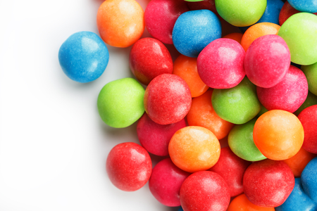 A rainbow of color from multicolored candies close-up, multi-colored glaze dragee on a white background. Bright colours